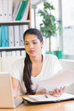 Businesswoman holding documents while using laptop Royalty Free Stock Image