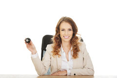 Businesswoman holding eight billiard ball. Businesswoman holding eight billiard ball by a desk Royalty Free Stock Images