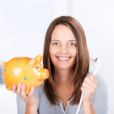Businesswoman Holding Electric Plug And Piggybank In Office Royalty Free Stock Photos
