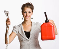 Businesswoman holding electrical plugs and gas can. Businesswoman holding up electrical plugs and gas can royalty free stock image