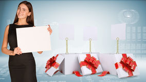 Businesswoman holding empty paper. Open gift boxes Stock Photos