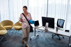 Businesswoman holding an exercise mat and looking her mobile phone Stock Photo
