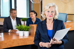 Businesswoman Holding File At Reception Counter Stock Image