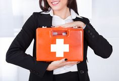 Businesswoman holding first aid box. Midsection of young businesswoman holding first aid box in office Stock Photo