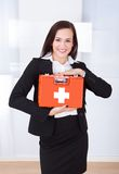 Businesswoman Holding First Aid Box. Portrait of confident young businesswoman holding first aid box in office Stock Photo