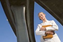 Businesswoman holding folder beneath overpasses, low angle view Stock Photo