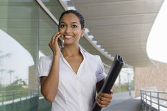 Businesswoman Holding Folder While On Call. An Indian businesswoman holding folder while on call Royalty Free Stock Photos