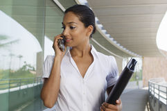 Businesswoman Holding Folder While On Call. An Indian businesswoman holding folder while communicating on mobile phone Royalty Free Stock Photos