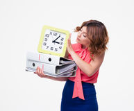 Businesswoman holding folders and looking on clock Royalty Free Stock Photo