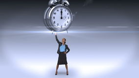 Businesswoman holding giant alarm clock. On grey background stock video footage