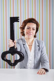 Businesswoman holding a giant key Stock Photos