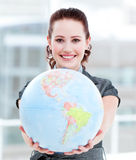 Businesswoman holding a globe. Charismatic businesswoman holding a terrestrial globe in the office Royalty Free Stock Photography
