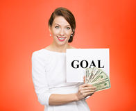 Businesswoman holding goal sign and money. Portrait smiling happy young businesswoman holding goal sign and cash, money isolated on red background. Positive stock image