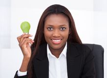 Businesswoman holding green electric bulb in office. Portrait of confident businesswoman holding green electric bulb in office royalty free stock images