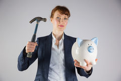Businesswoman holding hammer and piggy bank Royalty Free Stock Photos