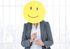 Businesswoman holding happy smiley face in front of her face against white background stock photo
