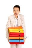 Businesswoman holding heavy bidners. Shocked businesswoman holding heavy bidners Royalty Free Stock Photos