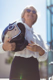 Businesswoman holding helmet on sunny day Stock Photo