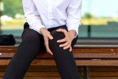 Businesswoman is holding her aching knee. While sitting on a bench stock image