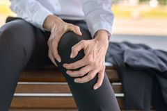 Businesswoman is holding her aching knee. While sitting on a bench stock photography
