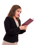 Businesswoman holding her agenda looking surprised. Young businesswoman  holding  her agenda and looking surprised on white Royalty Free Stock Photography
