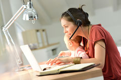 Businesswoman holding her baby and working on laptop Royalty Free Stock Photography