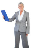 Businesswoman holding her clipboard and looking at camera Royalty Free Stock Image