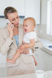 Businesswoman holding her crying baby talking on the phone Royalty Free Stock Photography