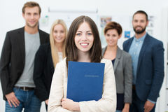 Businesswoman holding her curriculum vitae. Attractive smiling young businesswoman holding her curriculum vitae in a blue folder stock images
