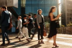 Businesswoman standing still on a busy street. Businesswoman holding her hand bag standing still on a busy street with people walking past her using mobile royalty free stock image