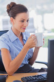 Businesswoman holding her mug and smiling Royalty Free Stock Photos