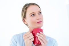 Businesswoman holding her mug and thinking Stock Images