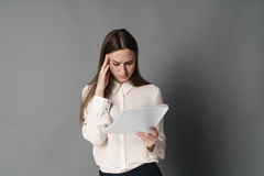 Businesswoman holding his head reading documents.  on gray background. Portrait of businesswoman. Royalty Free Stock Photos