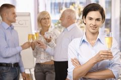 Businesswoman holding holding glass of champagne. Smiling businesswoman holding glass of champagne, looking at camera, coworkers celebrating in background Royalty Free Stock Photo
