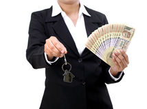 Businesswoman holding house key and currency Royalty Free Stock Image