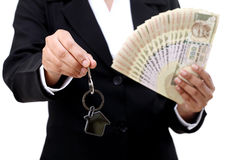 Businesswoman holding house key and currency notes Stock Image