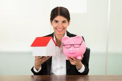 Businesswoman holding house model and piggybank Stock Image