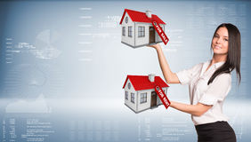 Businesswoman holding housees in hands Royalty Free Stock Images