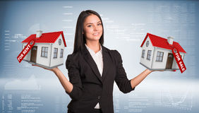 Businesswoman holding housees in hands Royalty Free Stock Photos