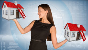 Businesswoman holding housees in hands Stock Images