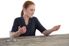 Businesswoman holding imaginary product. While sitting at table against white background Royalty Free Stock Photo