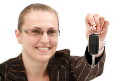 Businesswoman holding a key. A young attractive businesswoman offering car key to us, with smile on her face Stock Photos