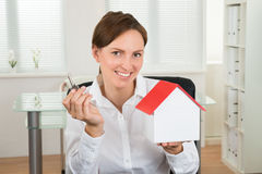 Businesswoman Holding Key And House Model Stock Photo