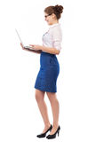 Businesswoman holding laptop. Young woman over white background royalty free stock image