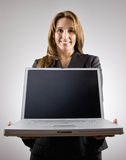 Businesswoman holding laptop. Confident businesswoman holding laptop smiling stock photo
