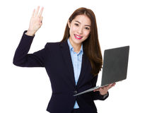 Businesswoman holding laptop computer and ok sign Stock Photo