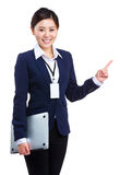 Businesswoman holding laptop computer and pointing up Stock Images