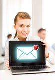 Businesswoman holding laptop with email sign Stock Photo