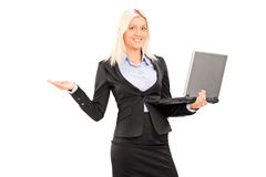 Businesswoman holding a laptop and gesturing Royalty Free Stock Image