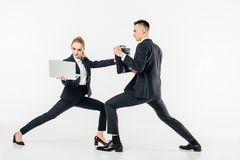 businesswoman holding laptop and kicking businessman in bag royalty free stock images